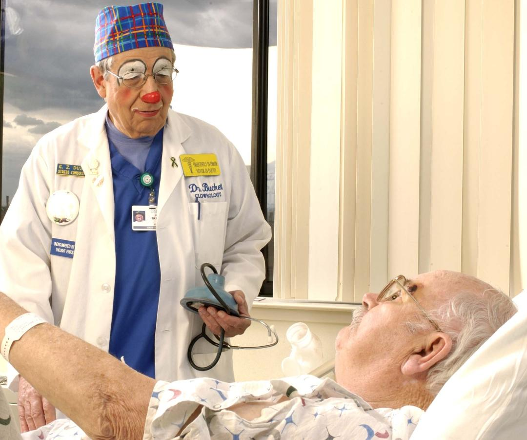 Clown speaking with a patient in bed.